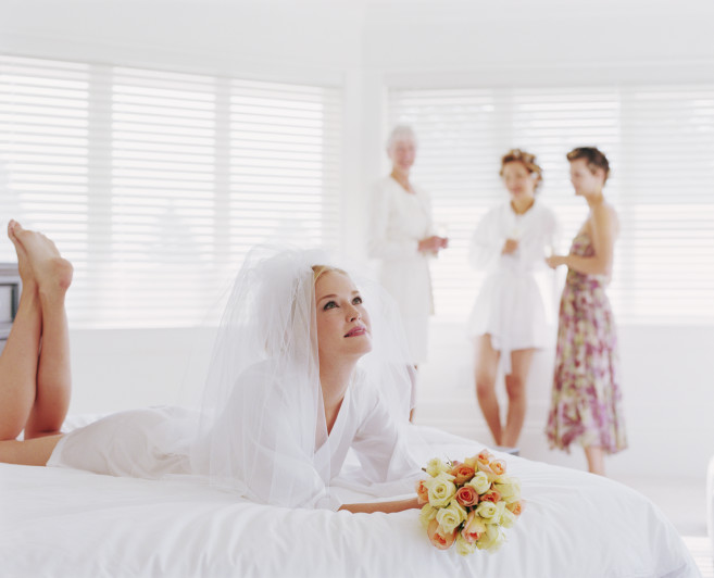 Bride and bridesmaids in bedroom (focus on bride lying on bed)